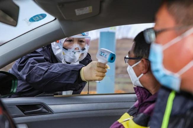山東榮成疾控中心人員對進城車輛的駕駛人員及乘客,檢測體溫。 (新華社)