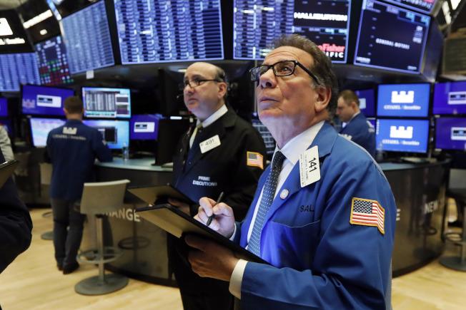 美股繼前一天大跌逾千點後,25日收盤繼續跌800多點,交易員緊張看著股票走勢。(美聯社)