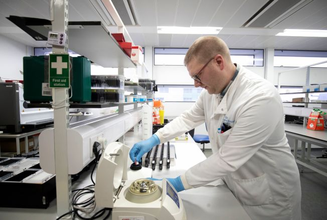 根據英國研究人員今天發表的一篇論文,不只老年人,中年人感染新冠肺炎後,演變為重症或死亡的風險也明顯偏高。圖為英國格拉斯哥皇家研究院科學家正在排列基因組合,對症下藥。(Getty Images)