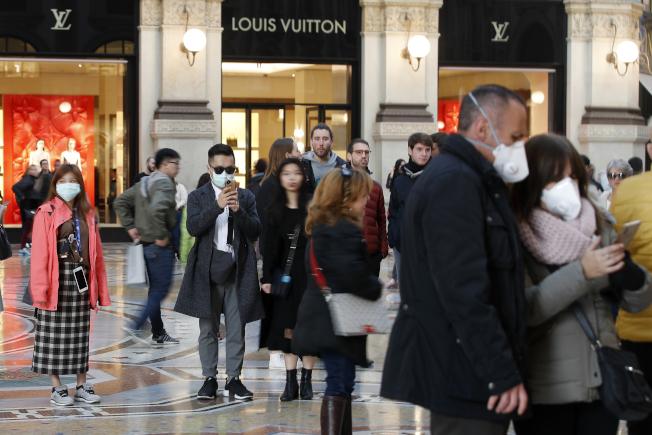 義大利米蘭民眾戴口罩逛街。 (美聯社)