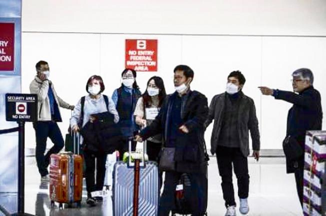 一批「口罩旅客」抵達舊金山機場。(美聯社)