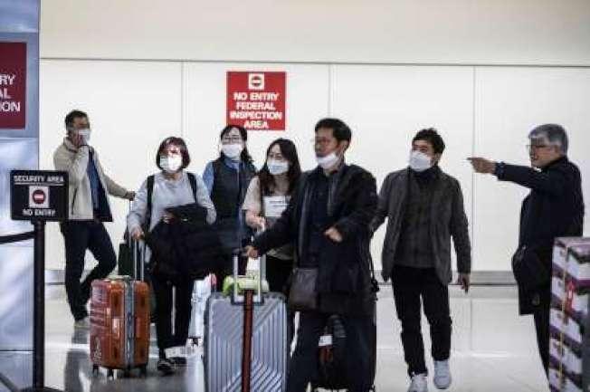 35--一批「口罩旅客」抵達舊金山機場。(美聯社)