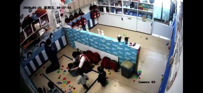 台南私立托嬰中心出現疑似虐童,畫面中的保母為了幫孩子戴口罩,用力拉扯孩子的兩耳。(取材自「靠北惡質幼兒園」臉書粉絲團)