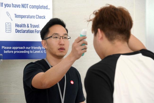 一名感染新冠炎的中國公民在新加坡謊報行蹤,被新加坡當局起訴。圖為新加坡教堂測量與會者體溫,非文中當事人。(Getty Images)