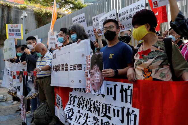 泛民主派26日在街頭集會,要求全民發錢,隨後財政司長陳茂波即宣布向18歲以上的香港永久性居民發放1萬港元。(路透)