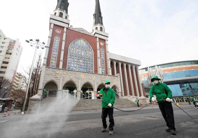 韓國首爾市的滿頌教會前,26日工作人員在消毒。韓國新冠疫情極為嚴重。(Getty Images)