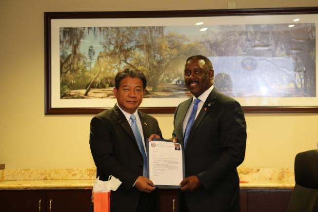 橘郡郡長德敏斯(Jerry Demings,右)頒贈歡迎賀函給台南市議會議長郭信良(左)。(孫博先提供)