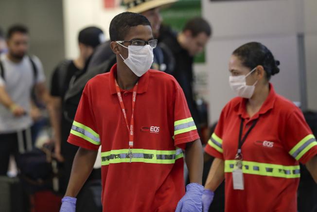 巴西出現首例新冠肺炎確診病例。圖為巴西國際機場內的員工戴上口罩。(美聯社)