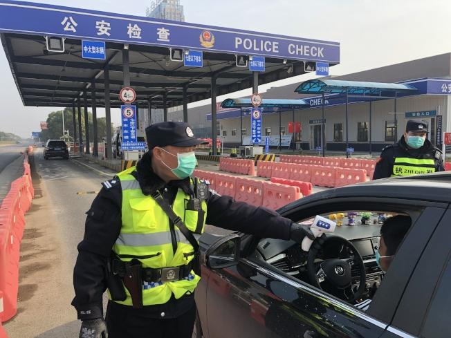 武漢解封3.5小時,究竟有多少人出城,引發網友關注。圖為武漢民警在公安檢查站執勤。(新華社)