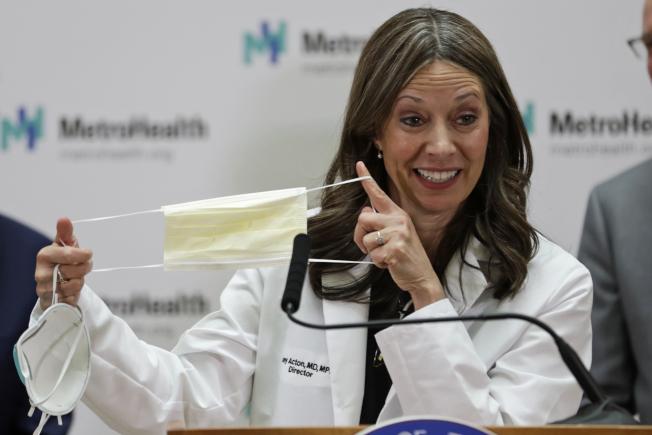 全美各州都進入防疫準備狀態,俄亥俄州衛生廳官員艾克頓27日在克里夫蘭市展示如何正確使用口罩。(美聯社)