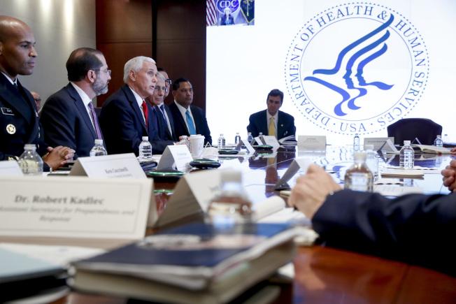 剛被川普總統指定擔心美國防疫最高協調人的潘斯副總統(紅領帶者)27日到衛生部協調中心瞭解情況,旁邊是衛生部長阿查爾。(美聯社)