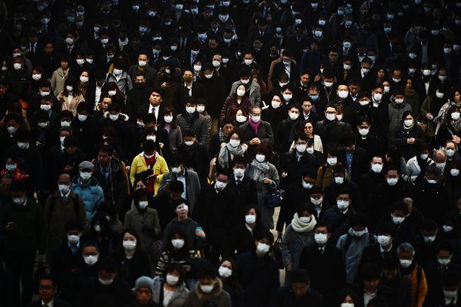 東京品川駅車站的28日上午通勤族,幾乎都戴著口罩,預防病毒。日本宣布各級學校停課一個月。(美聯社)
