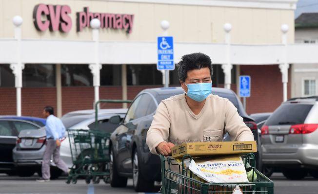 加州阿罕布拉的一位居民27日戴著口罩購物。北加州傳出本土第一件新冠病毒的確診病例。(Getty Images)