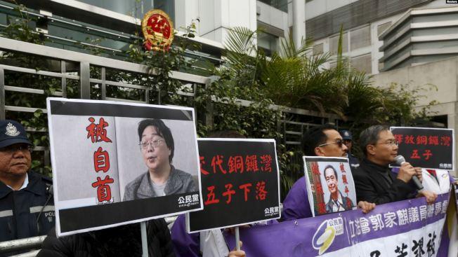 桂民海至今仍遭關押,美國促北京立刻無條件釋放。圖為香港抗議者在中聯辦前手舉桂民海的照片。(路透資料照片)