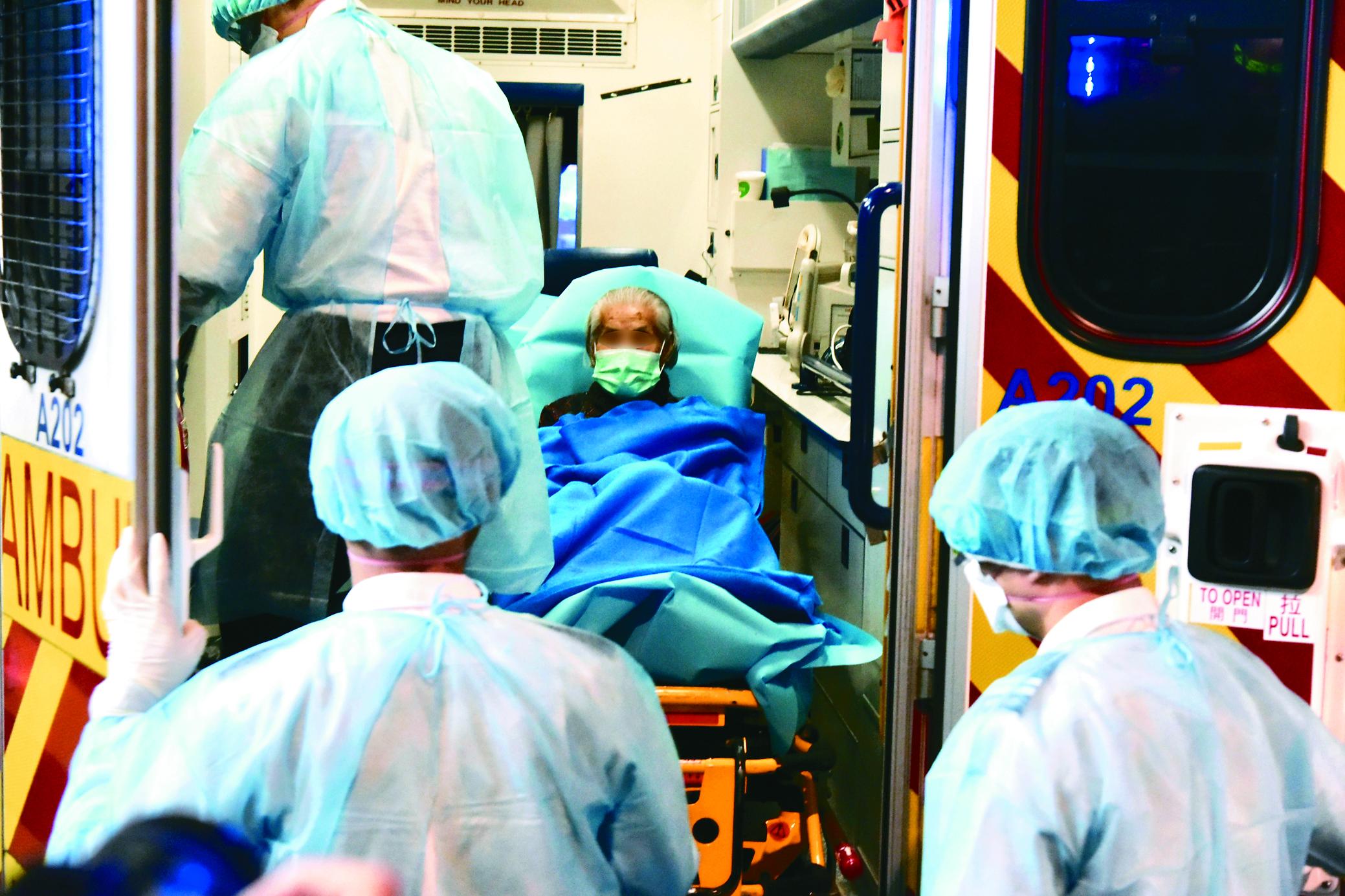香港北角美輪大廈23日晚上再有一人由身穿保護衣的救護人員協助下抬上救護車送醫。(中新社)