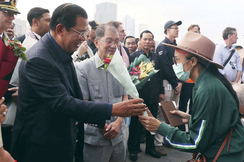柬國總理洪森(左)14日在港口迎接威士特丹號郵輪的乘客。(美聯社)