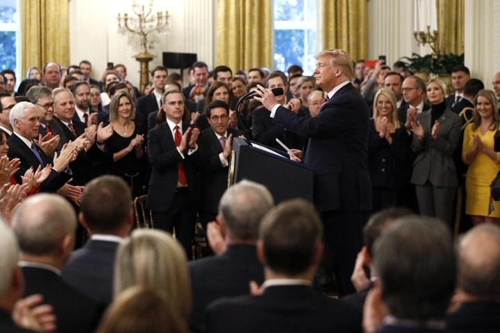 美國總統川普6日在白宮東廂舉行記者會,並拿出報導自己無罪的華爾街日報頭版,獲得支持者掌聲。(美聯社)