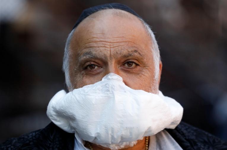 圖為紐約布魯克林一名男子,用一片尿布充當口罩蓋住鼻子和嘴巴。(路透)