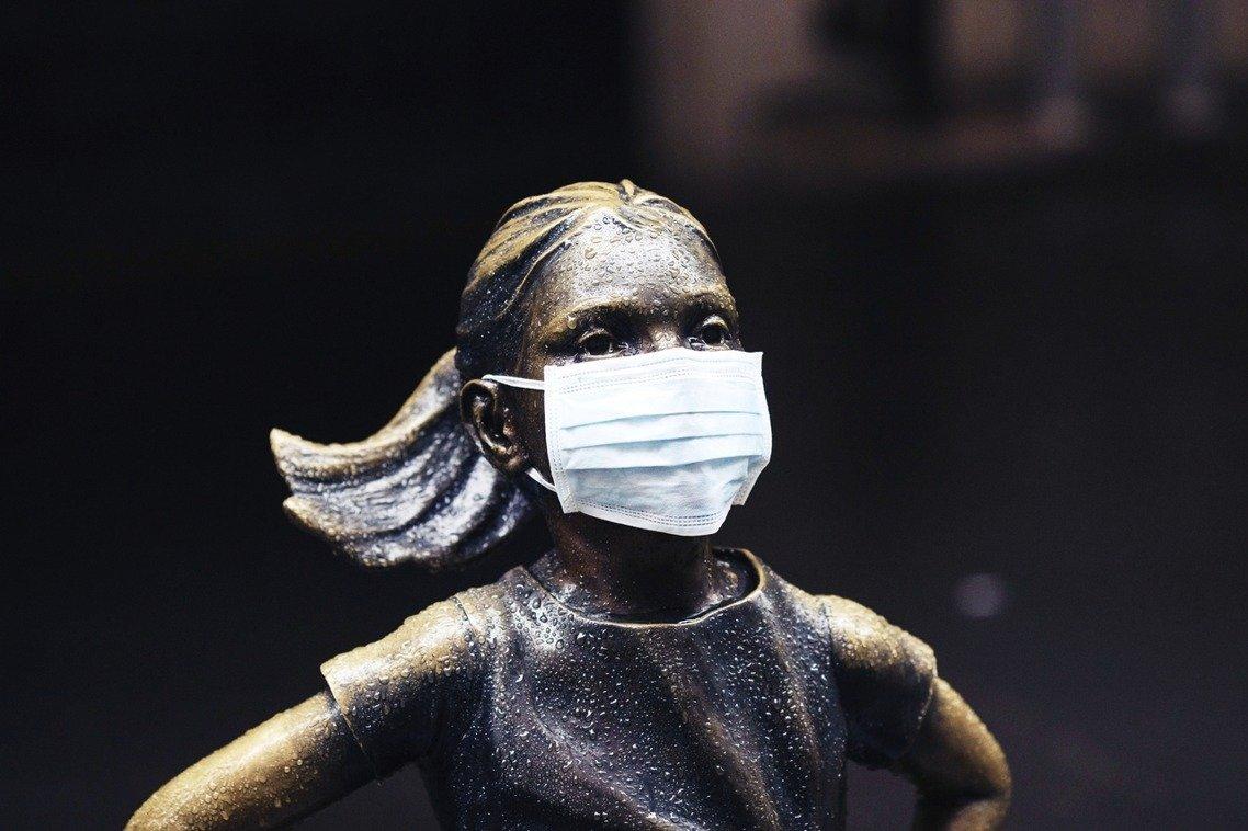 紐約證交所外的無畏女孩雕像也戴上口罩,在雨中略顯悲戚與堅毅。美聯社