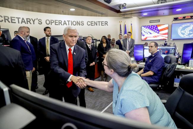 副總統潘斯上周巡視衛生與福利部抗疫行動中心,與工作人員握手。(美聯社)