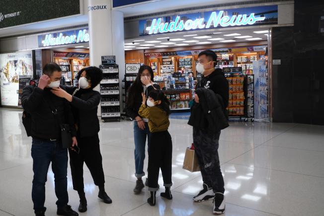 紐約甘逎迪機場(JFK),旅客戴上口罩防範感染新冠肺炎。(Getty Images)