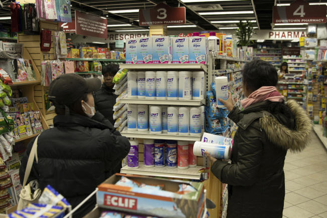 全美手部清潔劑短缺,兩名婦女在曼哈頓一家藥房選購消毒紙巾。(美聯社)
