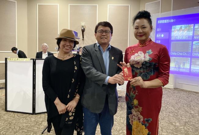 大奧蘭多台灣商會2020迎春聯歡會中抽獎之一,中獎人蕭維儒(中)與獎品贊助人嚴培達(右),左為顧問鄭蓮。(記者陳文迪/攝影)