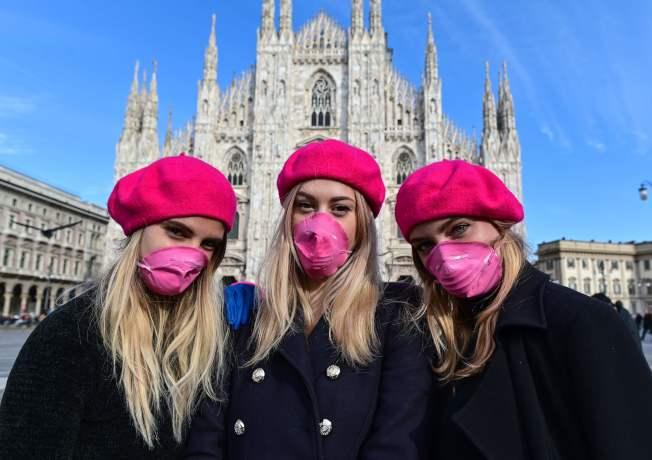 意大利,在疫情之下,民眾慶祝熱情仍高漲。圖中,三位女性戴上了象征女性的粉色毛線帽,口罩也染成了粉色。(Getty Images)