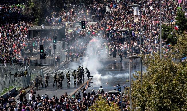 智利街頭不太平。在聖地亞哥舉行的國際婦女節遊行,隊伍人群與防暴警察發生衝突。(Getty Images)