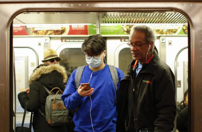 新冠病毒將在美國境內還將再蔓延一陣,近日各州都有報告首件確診病例。圖為紐約地鐵乘客戴著口罩。(美聯社)
