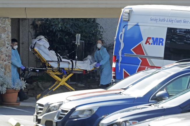 全美新冠病毒疫情的重災區在華盛頓州金恩郡的生命照護中心。全副裝備的醫務人員正在送一名病人上救護車。該中心9日又傳死亡病例。(美聯社)