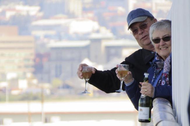 郵輪「至尊公主號」9日終於獲准停靠在加州奧克蘭港,非美國籍乘客可下船接受檢測。一對新澤西州的夫婦高興舉杯,慶祝上岸。(美聯社)