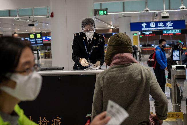 圖為北京機場海關檢查入境旅客證件。(Getty Images)