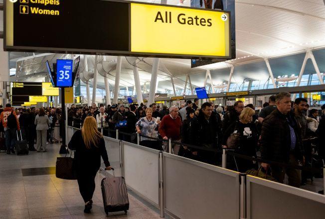 圖為紐約甘迺迪國際機場旅客排隊等安檢。(Getty Images)