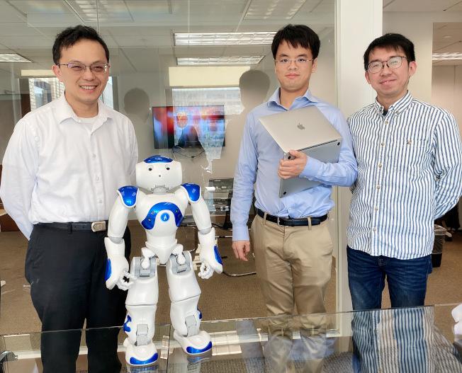 林清詠(右)和公司人員合影。桌上是研究用機器人Adam。(熊傳慧/攝影)
