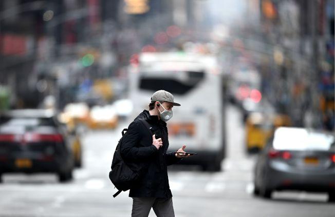 17日的時報廣場,一名男子戴口罩走在路上。(Getty Images)