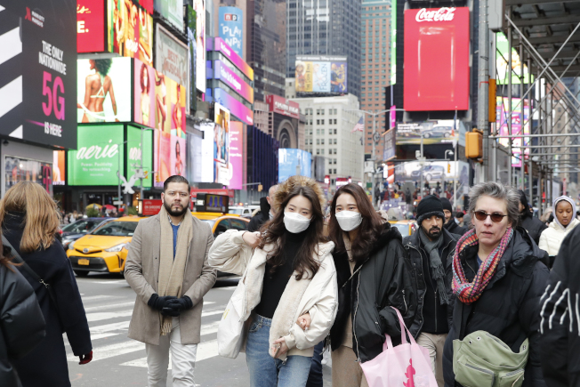 新冠疫情在紐約快速蔓延,愈來愈多民眾外出時戴口罩防疫。(中新社)
