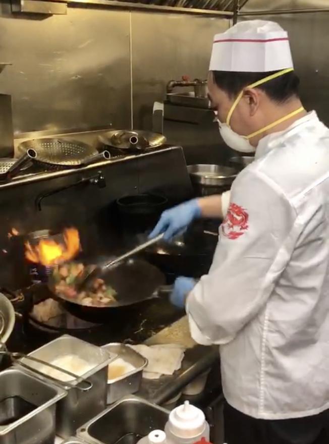 法拉盛「面對麵」餐館的廚師炒菜時會戴口罩和手套。(記者朱蕾/攝影)