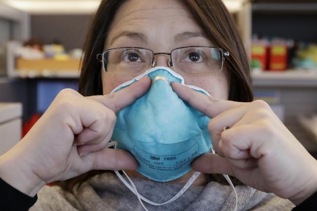 配戴口罩前先洗淨雙手,口罩有顏色的面朝外,金屬部位緊貼鼻樑,口罩包住下巴。(美聯社)