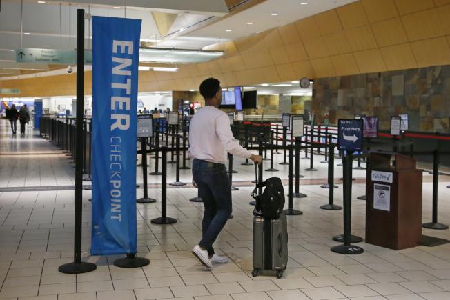 圖為奧克拉荷馬市羅傑斯機場的一名旅客走進空無一人的安檢通道。(美聯社)