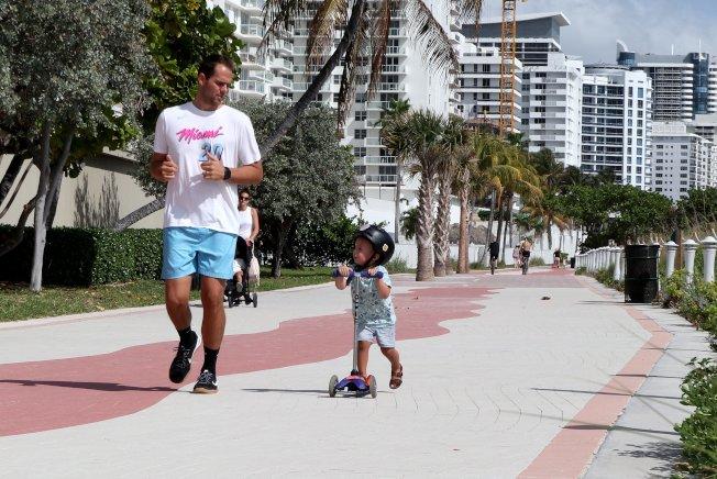 全美在經歷過一個異常溫和的冬天後,今年春季也將異於往常的溫暖。圖為一對父子在溫暖的陽光下跑步和騎踏板車。(美聯社)