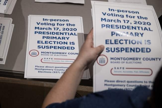 由於疫情影響,美國至少有13州延後初選投票。圖為俄亥俄州選務工作者分發「初選延遲」的通知。(Getty Images)