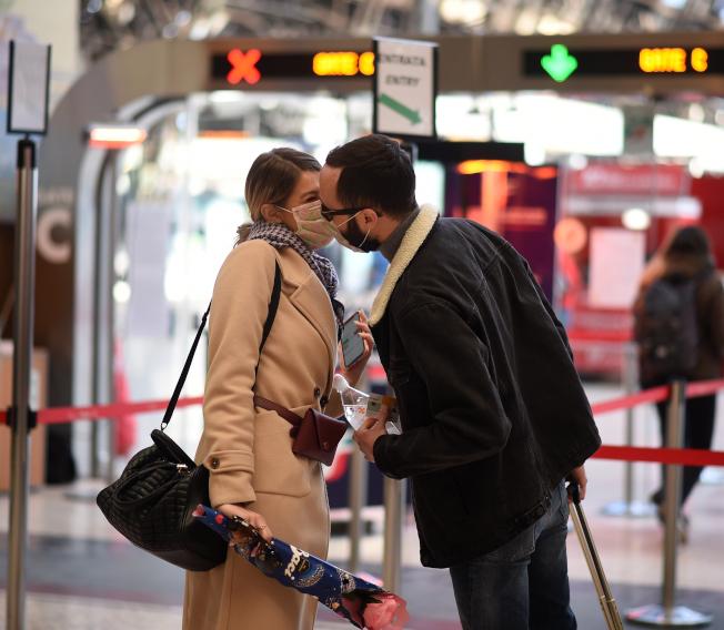 義大利人無視政府禁令,戴著口罩仍然在米蘭火車站親吻。(新華社)