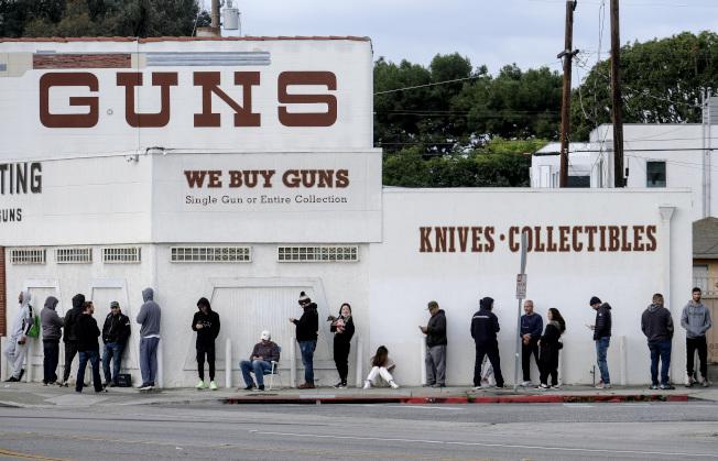 隨著新冠肺炎疫情蔓延緊張,各州相繼推出禁足令,讓人們提高自保意識,槍枝銷售大增。圖為日前在加州Culver市的槍店前排隊購槍的人龍。(美聯社)