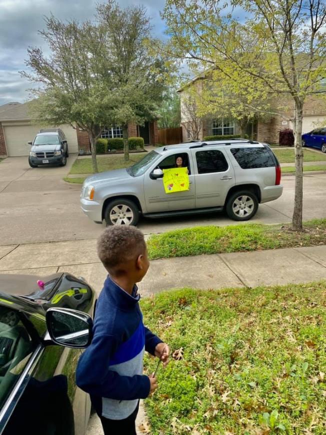 一名非裔男生看到老師向他秀海報好高興。(臉書照片)
