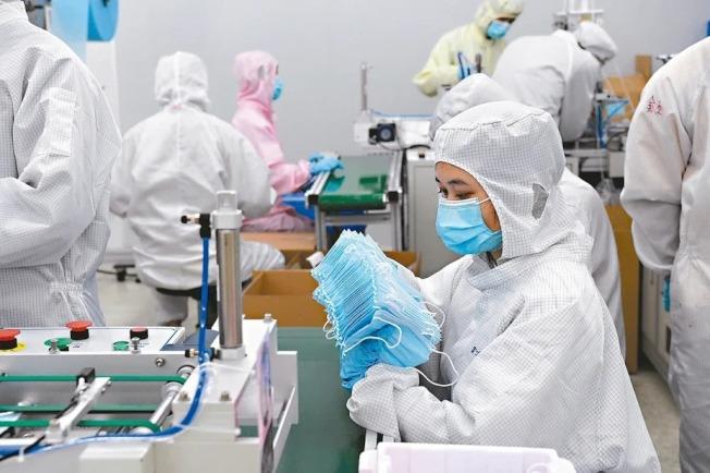 「口罩荒」在中國逐漸緩解,口罩廠商開始供應國際市場。根據賽迪智庫的調研,中國口罩產能將在未來達到日產2億片。 天眼查專業版數據顯示,截至3月22日,經營範圍含「口罩、呼吸防護」的企業數共有5萬2411家,其中自今年2月以來新增超6000家,與去年同期比較,增速高達16倍以上。在這5萬多家企業中,又有1萬7013家的經營範圍含進出口。圖為工人在富士康口罩生產車間工作。 (新華社)