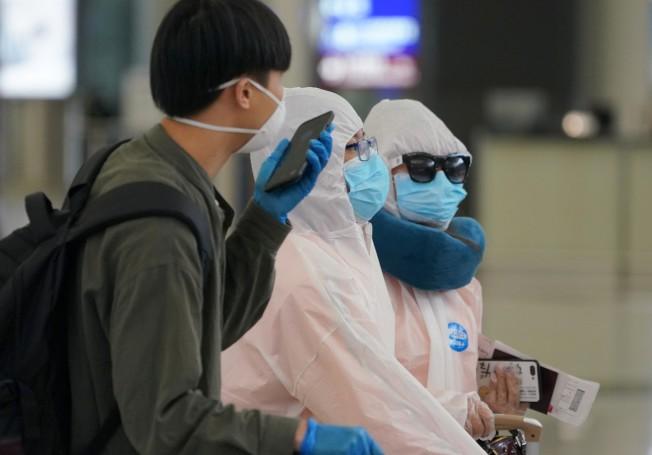 香港一周新增約200例 專家籲防疫不可鬆懈。圖為旅客搭乘國際航班抵達香港國際機場。(中通社)