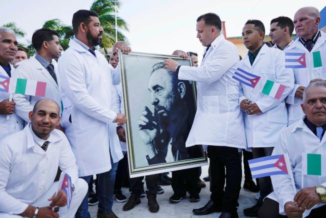 古巴也向義大利派出52名國家醫生。圖為古巴醫生出發前拿著革命領袖卡斯楚的相片。(路透)