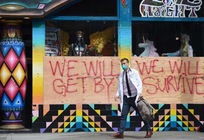 舊金山是全美第一個居家避疫的城市,圖為醫師至街友聚集處檢疫。其背景為「我們一定挺得過去」標語。(Getty Images)