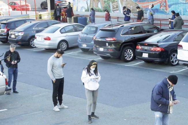 舊金山一家好市多門前,人們排隊,保持六呎距離。(取自推特)